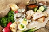 Pancetta, verdure fresche, uova sode e pane su carta, bicchieri con vodka su fondo in legno. concetto di colazione villaggio. — Foto Stock