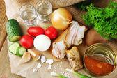 Slanina, čerstvá zelenina, vařené vejce a chléb na papíře, brýle s vodkou na dřevěné pozadí. obec snídaně koncept. — Stock fotografie