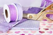 Ribbons with scissors and fabrics on bright background — Stock Photo
