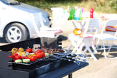 Skewers and vegetables on barbecue grill, close-up — Stock Photo