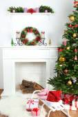 Fireplace with beautiful Christmas decorations in room — Stock Photo