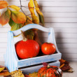 Pumpkins in wooden box and leaves on wooden table on wooden wall background — Stock Photo #55646259