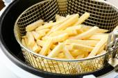 French fries in deep fryer — Stock Photo