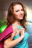 Beautiful young woman with shopping bags on bright background — Stock Photo