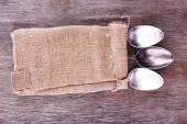 Tableware wrapped in sackcloth napkin on wooden background — Stock Photo