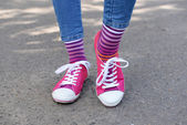 Female legs in colorful socks and sneakers — 图库照片