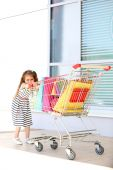 Happy little girl with shop bags in supermarket trolley, outdoors — Stock Photo