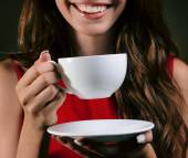 Beautiful young girl with cup of coffee on brown background — Stock Photo