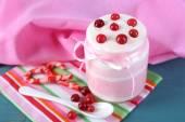 Raspberry milk dessert in glass jar, on color wooden background — Stock Photo