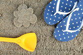 Flower-shaped wet sand and flip flops, close-up — Stockfoto