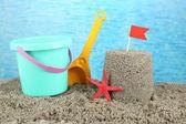 Sandcastle with flag and plastic bucket, spade on sandy beach  — Stock Photo