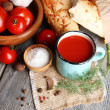 Homemade tomato juice in color mug, bread sticks, spices and fresh tomatoes — Stock Photo #56046471
