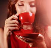 Beautiful young girl with cup of coffee on brown background — Stok fotoğraf