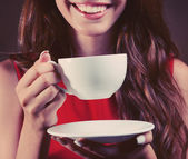 Beautiful young girl with cup of coffee on brown background — Photo