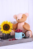 Toy bear and mug of raspberries on wooden tray on sackcloth on wooden wall background — Stock Photo