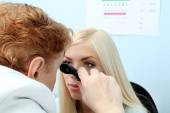 Optometry concept - pretty young woman having her eyes examined by eye doctor  — Stock Photo