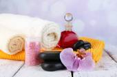 Still life with beautiful blooming orchid flower, spa set on color wooden table, on light background — Stock Photo