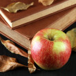 Apple with books and dry leaves on wooden background — Stock Photo #56106307