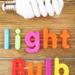 Light bulb word formed with colorful letters on wooden background — Stock Photo #56107183