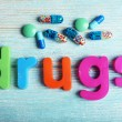 Drugs word formed with colorful letters on wooden background — Stock Photo #56107211