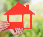 Woman hands holding paper house — Stock Photo