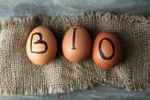 Eggs with inscription BIO on eggshell, on wooden background — Stock Photo