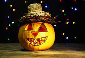 Halloween Pumpkin on table on dark background with multicolor lights — Stock Photo