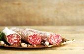 Italian salami on tray, on wooden background — Stock Photo