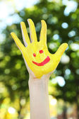 Smiling colorful hand on natural background — Stock Photo