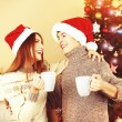 Nice love couple sitting with mugs in front of fireplace near Christmas tree. Woman and man celebrating Christmas — Stock Photo #56142033