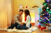 Nice love couple sitting on carpet in front of fireplace. Woman and man celebrating Christmas — Stock Photo