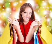 Shopping concept. Beautiful young woman with shopping bags on shop background — Foto Stock