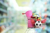 Shopping concept. Shopping cart with sport equipment on shop background — Stock Photo