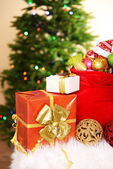 Red bag with Christmas toys on Christmas tree background — Stock Photo