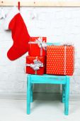 Christmas presents on blue chair on brick wall background — Stock Photo