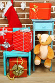 Christmas presents on chair and bookcase on brown brick wall background — Stock Photo