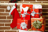 Christmas presents on chair on brown brick wall background — Stock Photo