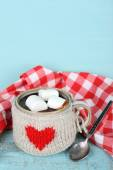 Cup of tasty hot cocoa, on wooden table, on color background — Foto Stock