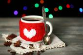 Cup of tasty hot tea, on wooden table, on shiny background — Foto Stock