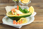Tasty salad with shrimps and avocado on plate, on wooden background — Stock Photo