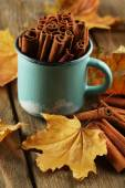Cinnamon sticks in mug with yellow leaves on wooden background — 图库照片