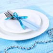 White plates, fork, knife and Christmas decoration on blue polka dot napkin on wooden background — Stock Photo #56343643
