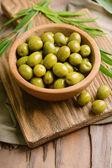 Zelené olivy v misce s listy na tabulka detail — Stock fotografie