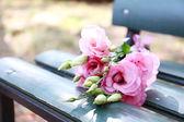 Piękny bukiet eustoma kwiatów na drewnianej ławce w parku — Zdjęcie stockowe