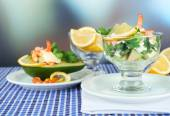 Tasty salads with shrimps and avocado in glass bowl and on plate, on table, on bright background — Stock Photo