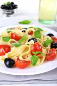Spaghetti with tomatoes, olives and basil leaves on plate on napkin on wooden table — Stock Photo
