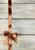 Old wooden background with beautiful bow — Stock Photo
