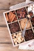 Wooden box with set of coffee and cocoa beans, sugar cubes, dark chocolate, cinnamon and anise, close-up, on wooden background — Stock Photo