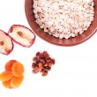Bowl of oatmeal, dried apricots and raisins isolated on white — Stock Photo #56352173