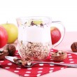 Oatmeal with yogurt in pitcher, apples and walnuts on polka dot napkin on pink wooden table on light background — Stock Photo #56352313